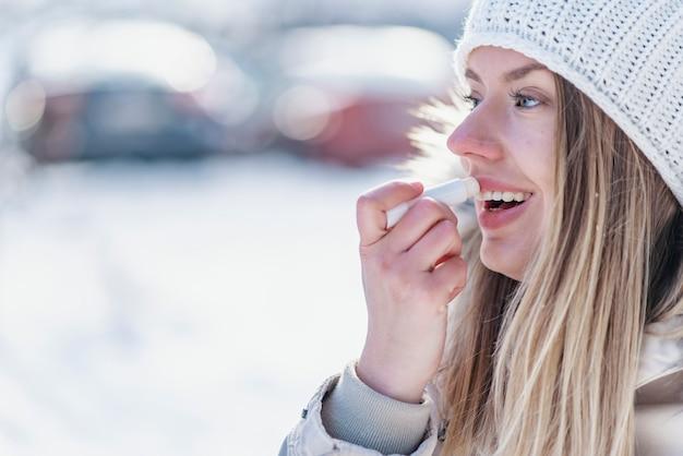 Retrato da fêmea nova que aplica o bálsamo de bordo no inverno.