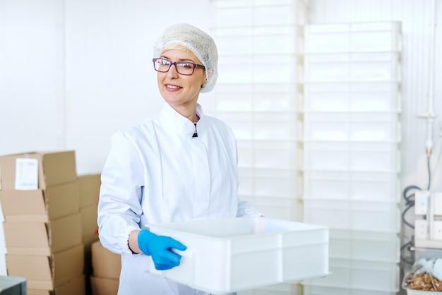 Retrato da funcionária loura de sorriso no uniforme estéril que relocating a caixa plástica. interior da fábrica de alimentos.
