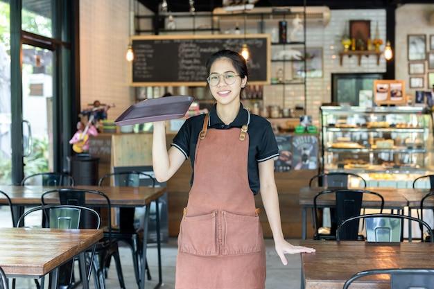 Retrato da garçom que guarda a bandeja vazia em uma cafetaria.