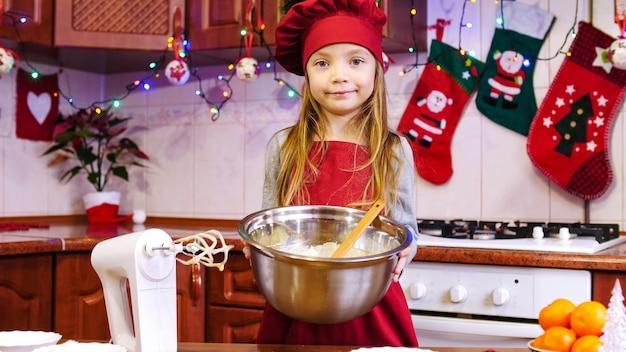 Retrato da garota do chef bonito mostrando para a câmera uma massa na tigela. na mesa estão batedeira, laranja, diversos ingredientes para massa