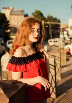 Retrato da gloriosa garota ruiva com sardas, usando óculos, posando sob a luz do sol