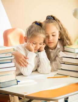 Retrato da irmã mais velha abraçando a mais nova e triste na aula