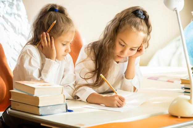 Retrato da irmã mais velha explicando o dever de casa para a mais nova