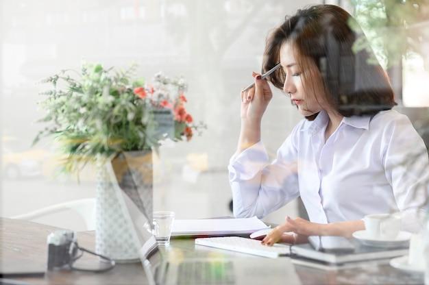 Retrato da jovem empresária segurando a caneta e pensando em novo projeto enquanto está sentado no escritório moderno, olhando através do vidro da janela.