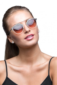 Retrato da jovem loira desportiva sexual usando óculos de sol.