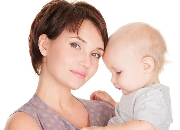 Retrato da jovem mãe bonita com bebê em fundo branco