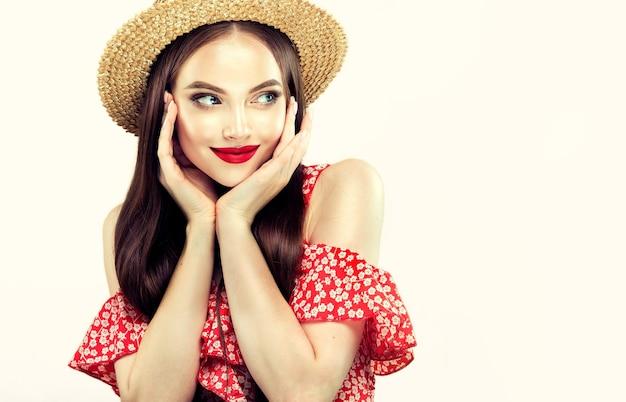Retrato da jovem modelo de cabelos compridos, vestida com um vestido de verão vermelho claro e um chapéu de palha. expressão facial agradável com sorriso terno nos lábios. maquiagem brilhante com batom vermelho no rosto.