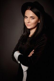 Retrato da jovem modelo mulher com maquiagem suave, usando um chapéu preto da moda e vestido preto por cima.