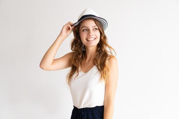 Retrato da jovem mulher à moda feliz que levanta no chapéu.
