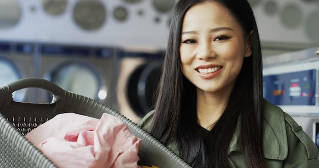 Retrato da jovem mulher asiática bonita que guarda a cesta com roupa limpa após lavar e sorrir para a câmera. perto da menina elegante bonita com sorriso na sala de serviço de lavanderia.