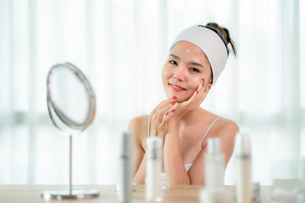 Retrato da jovem mulher asiática bonita que importa-se de sua pele que senta-se perto do espelho no quarto com a garrafa dos cuidados com a pele na tabela, rosto tocante da mulher. conceito de cuidados com a pele juventude beleza