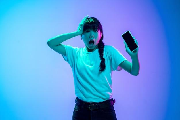 Retrato da jovem mulher asiática em fundo gradiente estúdio azul-roxo em luz de néon. conceito de juventude, emoções humanas, expressão facial, vendas, anúncio. bela modelo moreno.