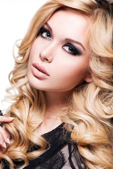 Retrato da jovem mulher bonita com cabelos cacheados loiros e maquiagem escura dos olhos. modelo de moda sobre fundo branco.