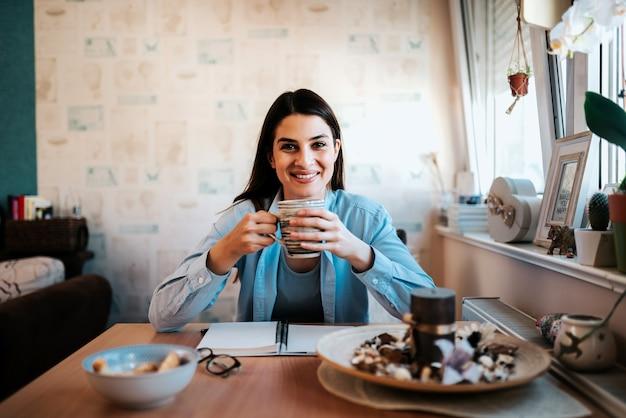 Retrato da jovem mulher bonita em seu café bebendo do apartamento.