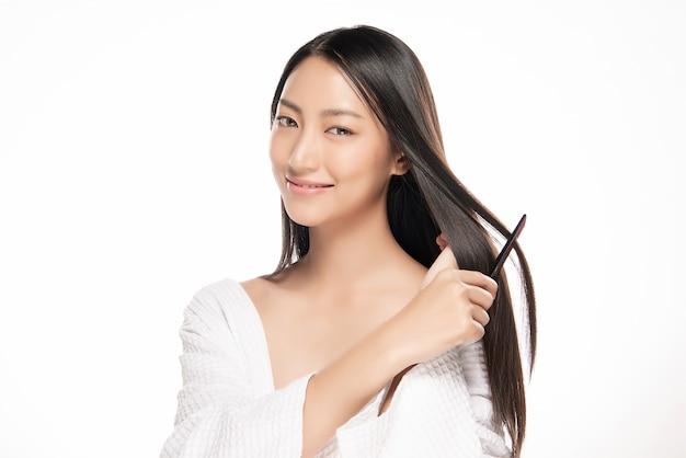 Retrato da jovem mulher bonita que penteia seu cabelo.