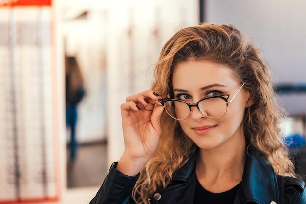 Retrato da jovem mulher bonita que tenta vidros novos na loja do ótico.