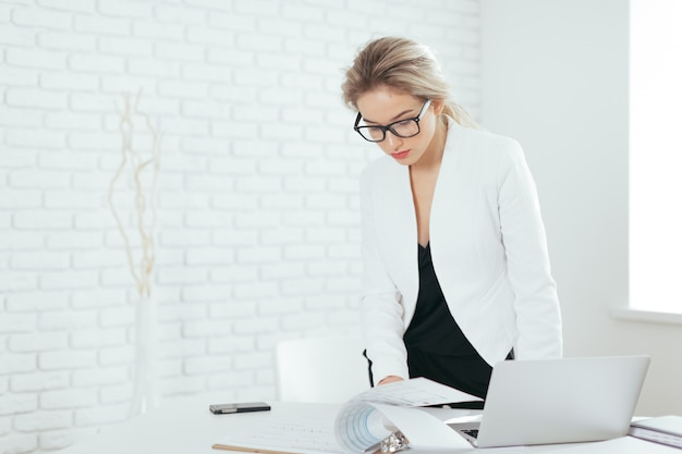 Retrato da jovem mulher bonita que trabalha no escritório.