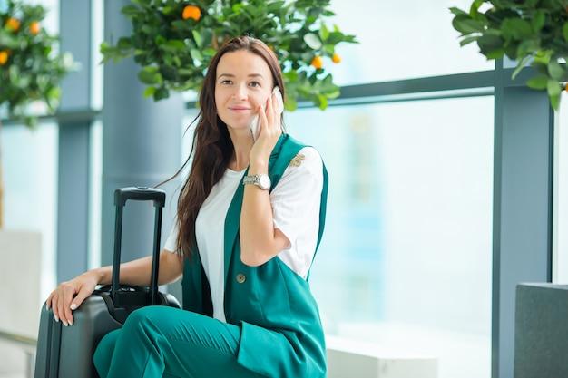 Retrato da jovem mulher com o smartphone no aeroporto internacional.