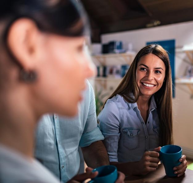 Retrato da jovem mulher de sorriso na ruptura de café com colegas de trabalho.