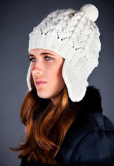 Retrato da jovem mulher em um boné de inverno no escuro
