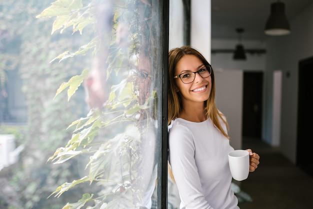 Retrato da jovem mulher encantador que inclina-se na janela. olhando para a câmera.