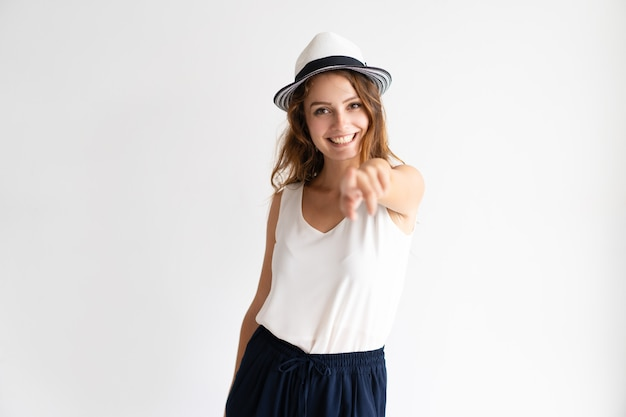 Retrato da jovem mulher feliz no chapéu que aponta na câmera.