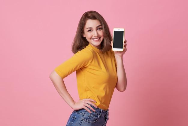 Retrato da jovem mulher feliz que mostra no telefone móvel de tela em branco isolado sobre o rosa.