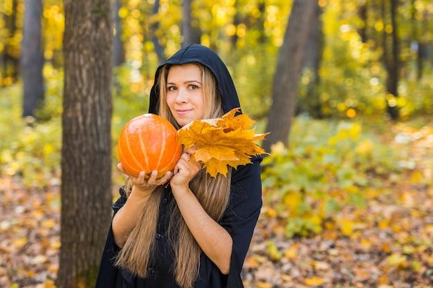 Retrato da jovem mulher loura bonita dramática que guarda a abóbora na floresta. dia das bruxas.