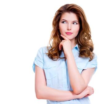 Retrato da jovem mulher pensando, olhando para cima de lado, isolado no fundo branco.