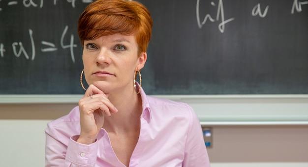 Retrato da jovem professora na lição da escola com quadro-negro