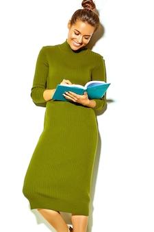 Retrato da linda feliz sorridente morena menina estudante em roupas de verão casual hipster verde isolado no branco escrevendo no caderno colorido azul, pensando enquanto estudava