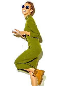 Retrato da linda feliz sorridente mulher morena bonita garota com roupas de verão casual hipster verde isolado no branco em óculos de sol, ouvindo música no smartphone com fones de ouvido