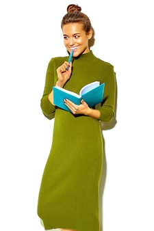 Retrato da linda feliz sorridente mulher morena menina bonita em roupas de verão hipster verde casual isolado no branco mordendo caneta azul com caderno colorido