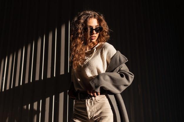 Retrato da luz do sol de um modelo de menina linda com cabelos cacheados em roupas da moda com um casaco, blusa de malha e óculos de sol vintage na cidade. estilo urbano feminino