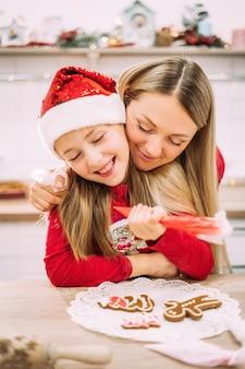 Retrato da mãe abraçando a filha por ajudá-la a decorar os biscoitos de gengibre