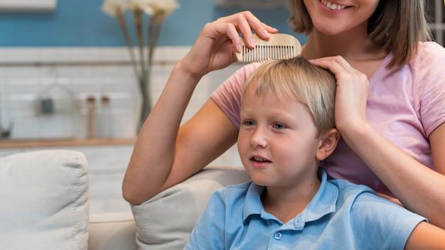 Retrato da mãe arrumando o cabelo do filho
