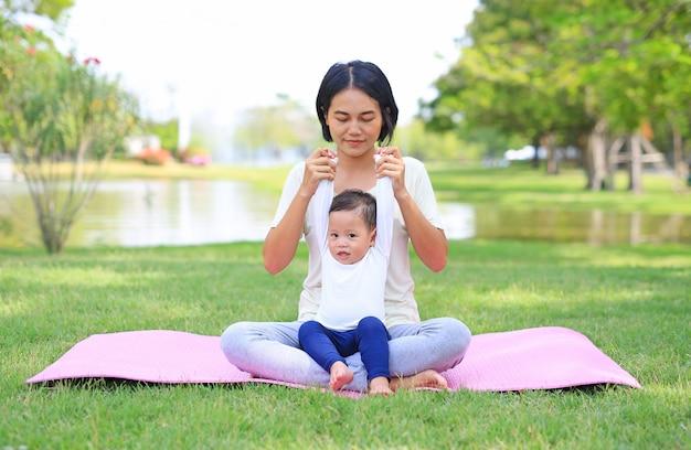 Retrato da mãe asiática que faz o exercício para seu filho no gramado verde no jardim da natureza ao ar livre.