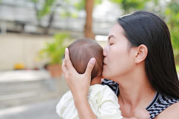 Retrato da mãe asiática que leva e que beija seu bebê infantil exterior.