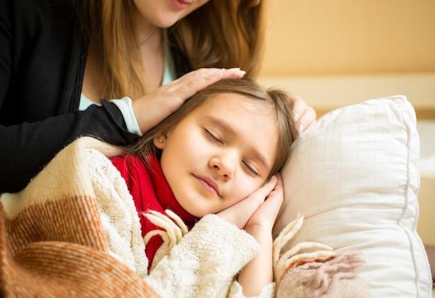 Retrato da mãe segurando a mão na cabeça da filha adormecida