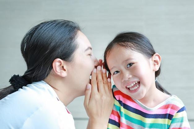 Retrato da mamã feliz que sussurra um segredo algo a sua orelha pequena da filha.
