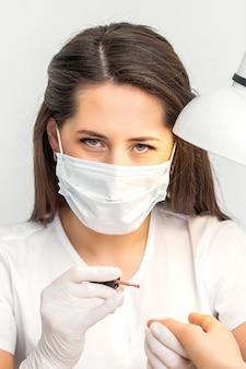 Retrato da manicure master com máscara protetora branca trabalhando em salão de beleza