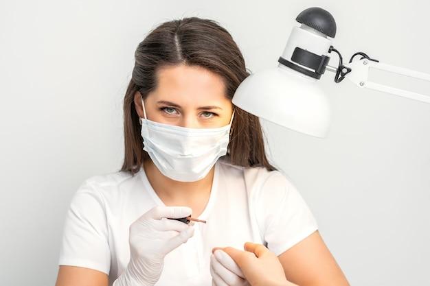 Retrato da manicure master com máscara protetora branca trabalhando em um salão de beleza