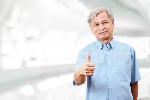 Retrato da mão asiática superior feliz do gesto do homem que mostra o polegar acima.