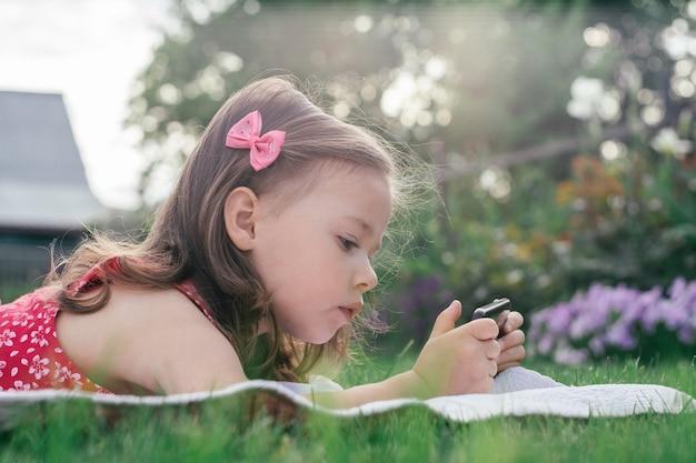 Retrato da menina 3-4 em vermelho deitado no cobertor na grama verde e olhando para o telefone móvel. crianças usando gadgets