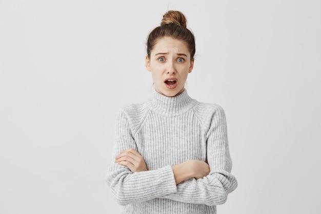 Retrato da menina adulta indignada que está na postura fechada com a boca aberta. hipster feminino se ressentindo de sua amiga fizeram em pé com as mãos cruzadas. conceito de expressões