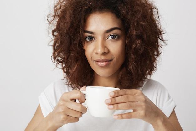 Retrato da menina africana bonita que sorri guardando a xícara de café.