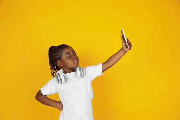 Retrato da menina afro-americana isolado no estúdio amarelo