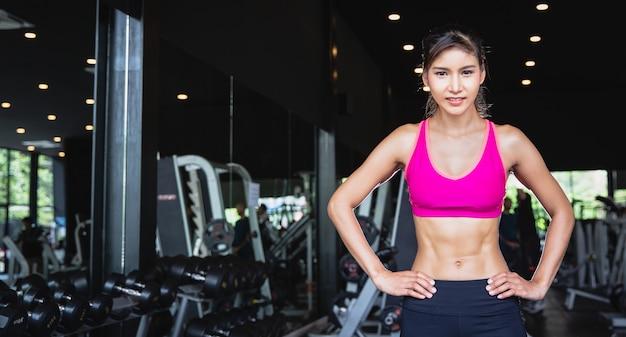 Retrato da menina asiática bonita nova com seis blocos no sportswear que está e que cruza os braços no gym da aptidão com espaço da cópia. fitness malhar e conceito de saúde yoga