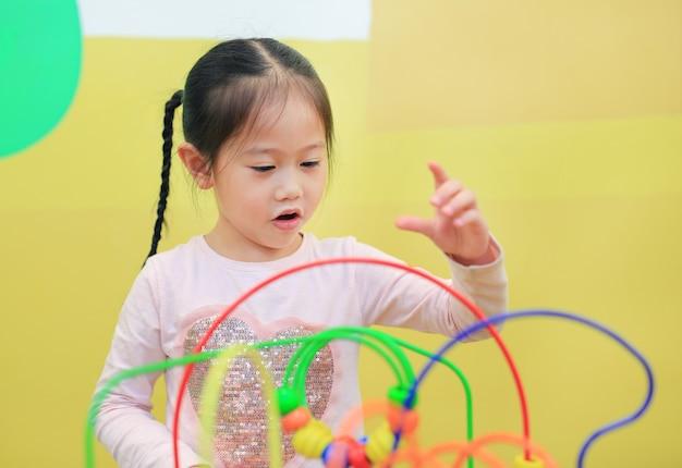 Retrato da menina asiática da criança que joga o brinquedo educacional para o desenvolvimento do cérebro na sala das crianças.