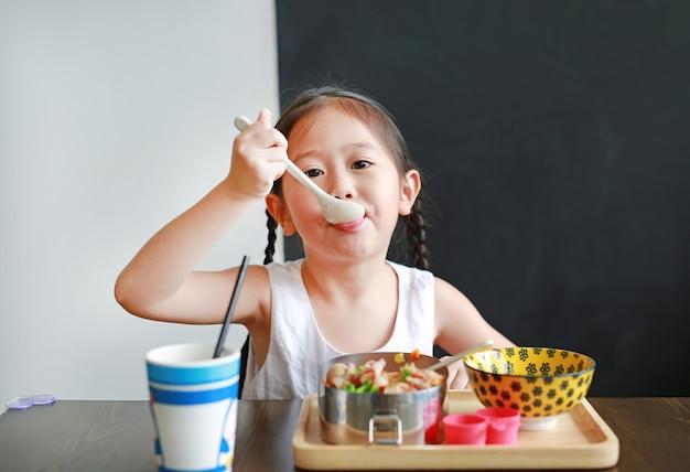 Retrato da menina asiática pequena da criança que come o café da manhã na manhã.